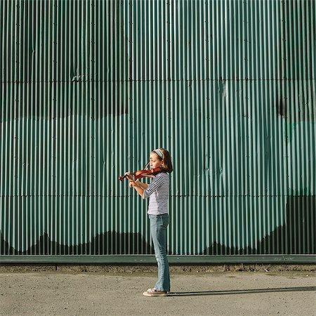 A ten year old girl playing the violin on an urban street. Stock Photo - Premium Royalty-Free, Code: 6118-07203256