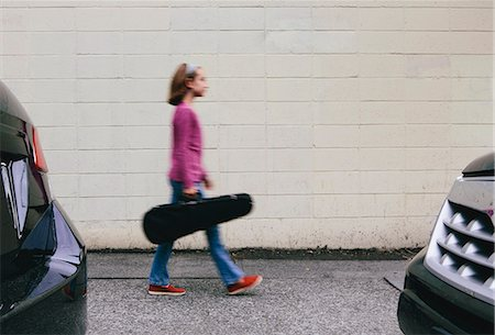 A ten year old girl carrying a violin in a case on an urban street. Stock Photo - Premium Royalty-Free, Code: 6118-07203259