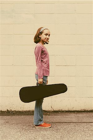 A ten year old girl carrying a violin in a case on an urban street. Stock Photo - Premium Royalty-Free, Code: 6118-07203260