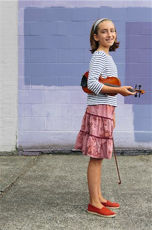 A ten year old girl holding a violin under her arm and a bow in her hand. Stock Photo - Premium Royalty-Free, Code: 6118-07203262