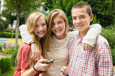farm phone - Three young people, two girls and a boy, posing and taking selfy photographs. Stock Photo - Premium Royalty-Free, Code: 6118-07203277