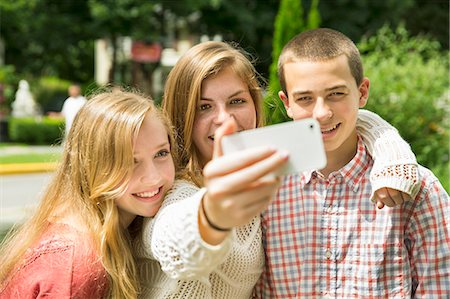 farm phone - Three young people, two girls and a boy, posing and taking selfy photographs. Stock Photo - Premium Royalty-Free, Code: 6118-07203278