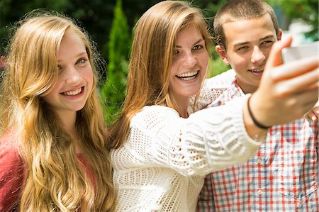Three young people, two girls and a boy, posing and taking selfy photographs. Stock Photo - Premium Royalty-Free, Code: 6118-07203279