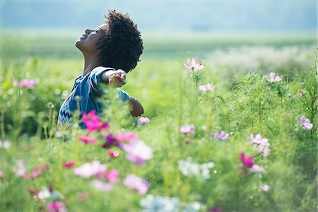 release - A woman standing among the flowers with her arms outstretched. Pink and white cosmos flowers. Stock Photo - Premium Royalty-Free, Code: 6118-07203350