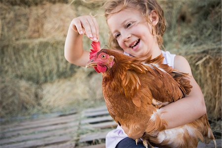 A young girl holding a chicken in a henhouse. Stock Photo - Premium Royalty-Free, Code: 6118-07203310