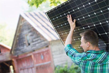 solar panel usa - A man carrying a solar panel towards a building under construction. Stock Photo - Premium Royalty-Free, Code: 6118-07203460