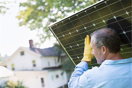 solar panel usa - A man carrying a solar panel towards a building under construction. Stock Photo - Premium Royalty-Free, Code: 6118-07203461