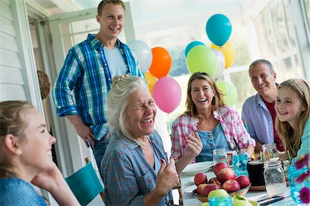 A birthday party in a farmhouse kitchen. A group of adults and children gathered around a chocolate cake. Stock Photo - Premium Royalty-Free, Code: 6118-07203418