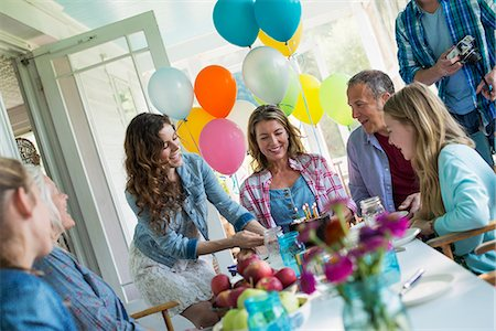 A birthday party in a farmhouse kitchen. A group of adults and children gathered around a chocolate cake. Stock Photo - Premium Royalty-Free, Code: 6118-07203419