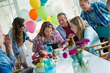 A birthday party in a farmhouse kitchen. A group of adults and children gathered around a chocolate cake. Stock Photo - Premium Royalty-Free, Code: 6118-07203421