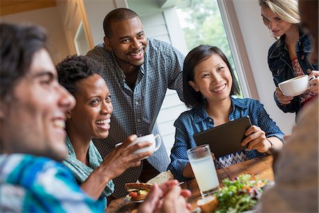 A group of people meeting in a cafe. Using digital tablets and smart phones. Stock Photo - Premium Royalty-Free, Code: 6118-07203664
