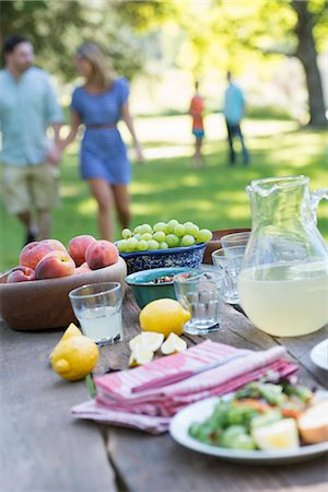 A summer buffet of fruits and vegetables, laid out on a table. People in the background. Stock Photo - Premium Royalty-Free, Code: 6118-07203624