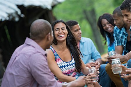 A group of men and women outdoors enjoying themselves. Stock Photo - Premium Royalty-Free, Code: 6118-07203761