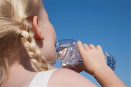 A young child with blonde hair in pigtails, drinking water from a clear bottle. Stock Photo - Premium Royalty-Free, Code: 6118-07203840