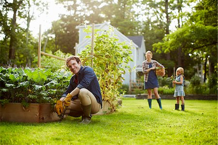 Three people, two adults and a child in a vegetable garden. Stock Photo - Premium Royalty-Free, Code: 6118-07203931