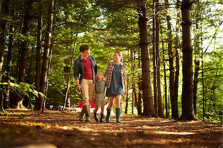 Three people, a family walking in woodland in the late afternoon. Stock Photo - Premium Royalty-Free, Code: 6118-07203937