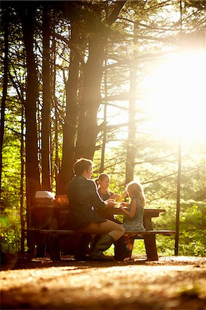 Three people, a family sitting at a picnic table under trees, in the late afternoon. Stock Photo - Premium Royalty-Free, Code: 6118-07203936