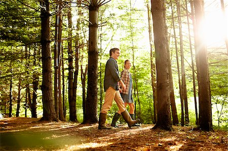 Three people, a family walking in woodland in the late afternoon. Stock Photo - Premium Royalty-Free, Code: 6118-07203938