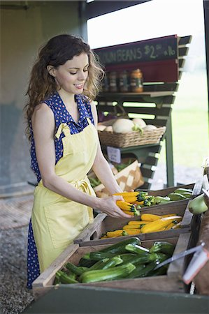 An organic fruit and vegetable farm. A young woman sorting vegetables. Stock Photo - Premium Royalty-Free, Code: 6118-07235198