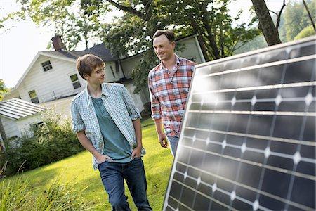 solar panel usa - Two people walking towards a farmhouse garden. Stock Photo - Premium Royalty-Free, Code: 6118-07235249