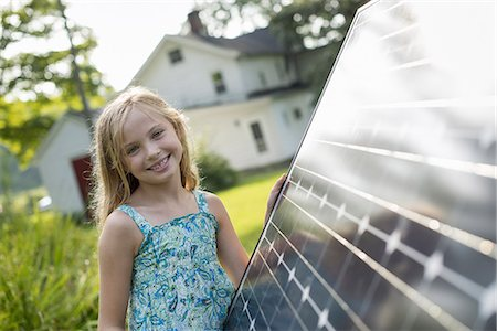 A young girl beside a large solar panel in a farmhouse garden. Stock Photo - Premium Royalty-Free, Code: 6118-07235257