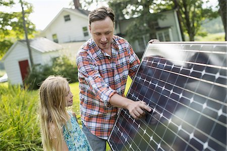 solar panel usa - A man and a young girl looking at a solar panel in a garden. Stock Photo - Premium Royalty-Free, Code: 6118-07235254