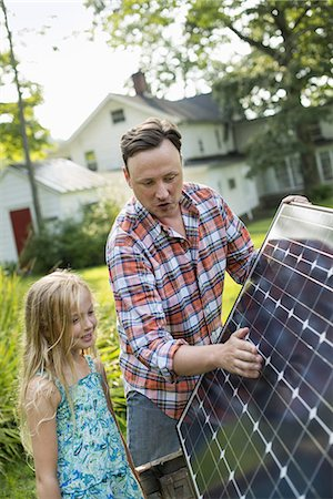 solar panel usa - A man and a young girl looking at a solar panel in a garden. Stock Photo - Premium Royalty-Free, Code: 6118-07235255