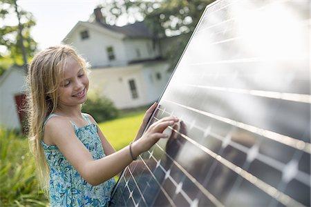 solar panel usa - A young girl beside a large solar panel in a farmhouse garden. Stock Photo - Premium Royalty-Free, Code: 6118-07235256