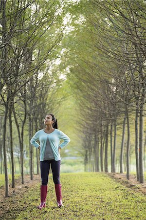 A woman between two rows of trees, looking upwards. Stock Photo - Premium Royalty-Free, Code: 6118-07235272