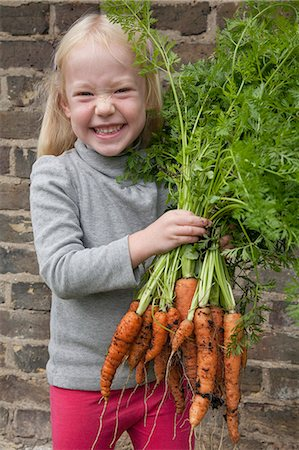 A young girl holding a large bunch of carrots. Stock Photo - Premium Royalty-Free, Code: 6118-07351143