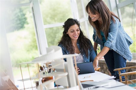 designer (female) - Two women working together, looking at the screen of a digital tablet. Stock Photo - Premium Royalty-Free, Code: 6118-07351177