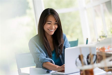 east asian - A woman in an office, working at a laptop computer. Stock Photo - Premium Royalty-Free, Code: 6118-07351181