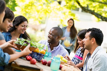 Adults and children around a table in a garden. Stock Photo - Premium Royalty-Free, Code: 6118-07351199