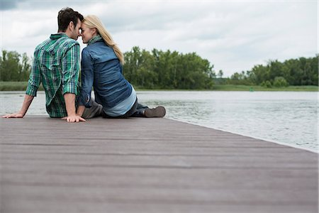 A man and woman seated on a jetty by a lake. Stock Photo - Premium Royalty-Free, Code: 6118-07351266