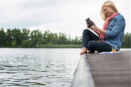 A woman sitting on a jetty by a lake, using a digital tablet. Stock Photo - Premium Royalty-Free, Code: 6118-07351272