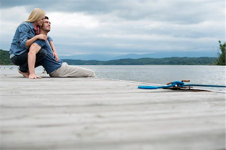 A man and woman seated on a jetty by a lake. Stock Photo - Premium Royalty-Free, Code: 6118-07351275