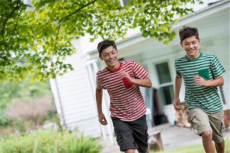 Two boys in a farmhouse garden in summer. Stock Photo - Premium Royalty-Free, Code: 6118-07351227