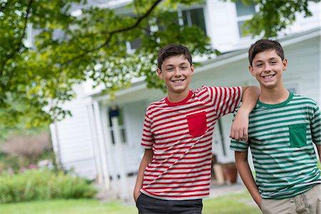Two boys in a farmhouse garden in summer. Stock Photo - Premium Royalty-Free, Code: 6118-07351226