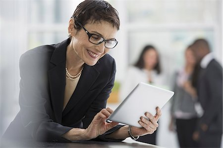 An office interior. A woman in a black jacket using a digital tablet. Stock Photo - Premium Royalty-Free, Code: 6118-07351357