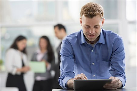 settlement - Young professionals at work. A man in an open necked shirt using a digital tablet. A group of men and women in the background. Stock Photo - Premium Royalty-Free, Code: 6118-07351361