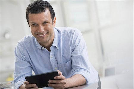 settlement - A man in a blue shirt leaning on a desk, holding a digital tablet. Stock Photo - Premium Royalty-Free, Code: 6118-07351368
