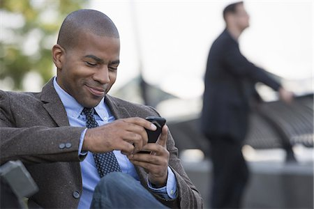 settlement - Business people in the city. Keeping in touch on the move. A man seated using his smart phone. A man in the background. Stock Photo - Premium Royalty-Free, Code: 6118-07351481
