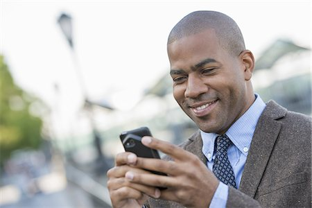 settlement - Business people in the city. Keeping in touch on the move. A man using a smart phone. Stock Photo - Premium Royalty-Free, Code: 6118-07351485