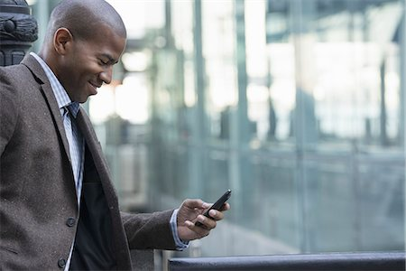 settlement - Business people in the city. Keeping in touch on the move. A man standing outdoors checking his cell phone. Stock Photo - Premium Royalty-Free, Code: 6118-07351493
