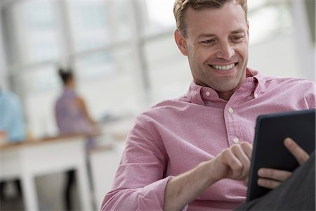person - An open plan office in New York City.  A man in a pink shirt sitting smiling, using a digital tablet. Stock Photo - Premium Royalty-Free, Code: 6118-07351435