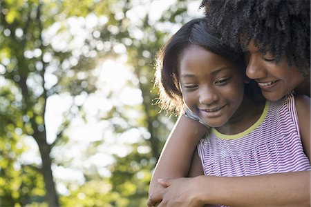 A young woman and a child hugging. Stock Photo - Premium Royalty-Free, Code: 6118-07351599