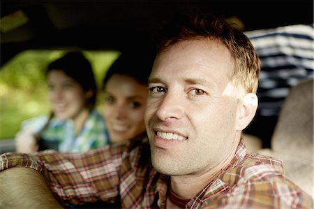 Three passengers in the cab of a pickup truck. One young man driving. Two young women sitting beside him. Stock Photo - Premium Royalty-Free, Code: 6118-07351670