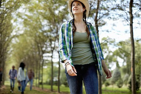 A girl in a straw hat walking in the woods. Stock Photo - Premium Royalty-Free, Code: 6118-07351613