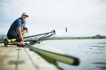 side view of person rowing in boat - A middle-aged man on a jetty preparing a rowing boat for an outing. Stock Photo - Premium Royalty-Free, Code: 6118-07351859
