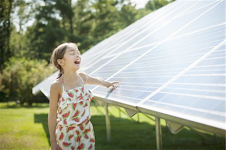 solar panel usa - A child in the fresh open air on a sunny day, beside solar panels at a farm in New York State, USA. Stock Photo - Premium Royalty-Free, Code: 6118-07351945